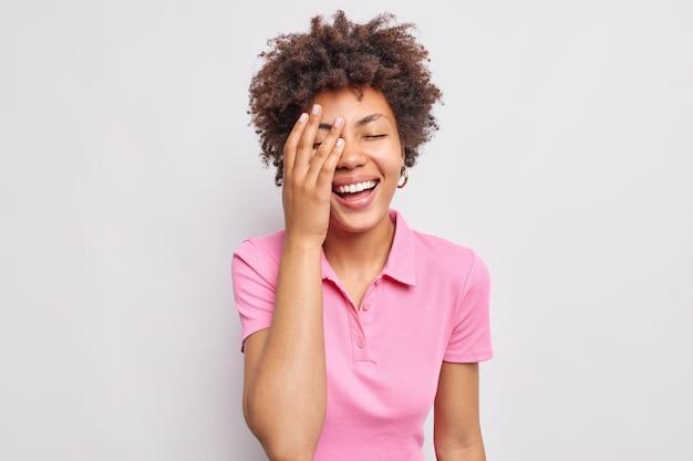Rozradowana młoda kobieta sprawia, że twarz dłoni chichocze pozytywnie, czuje się zadowolona, nie ukrywa swoich pozytywnych autentycznych emocji, ubrana niedbale na białym tle na białej ścianie