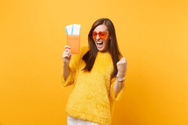 Rozradowana młoda kobieta w okularach z pomarańczowym sercem krzyczy, robi gest zwycięzcy, trzymając bilety na pokład paszportu na białym tle na żółtym tle. ludzie szczere emocje styl życia. powierzchnia reklamowa.