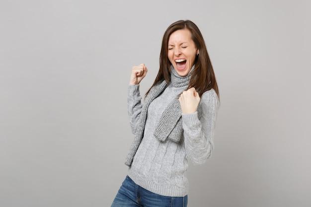 Rozradowana młoda kobieta w szarym swetrze, szalik z zamkniętymi oczami krzyczy, robi gest zwycięzcy na białym tle na tle szarej ściany. zdrowy styl życia moda, szczere emocje ludzi, koncepcja zimnej pory roku.