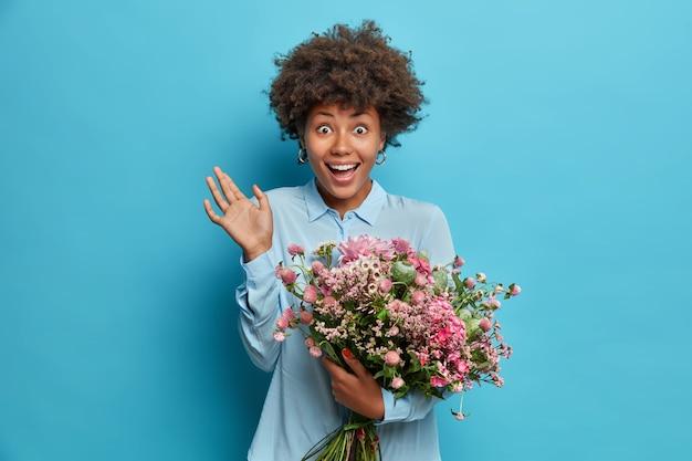 Rozradowana młoda kobieta z kręconymi włosami podnosi dłoń i czuje się bardzo zadowolona, gdy podnosi dłoń obejmując duży bukiet kwiatów ubrana w świąteczny strój odizolowany na niebieskiej ścianie studia