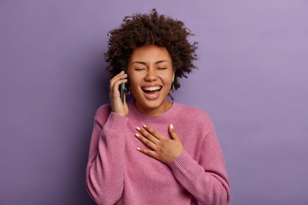 Rozradowana nastolatka śmieje się podczas rozmowy telefonicznej, trzyma rękę na piersi, nie może przestać chichotać, trzyma telefon przy uchu, słyszy śmieszny dowcip, zamyka oczy, modelki w domu na fioletowej ścianie