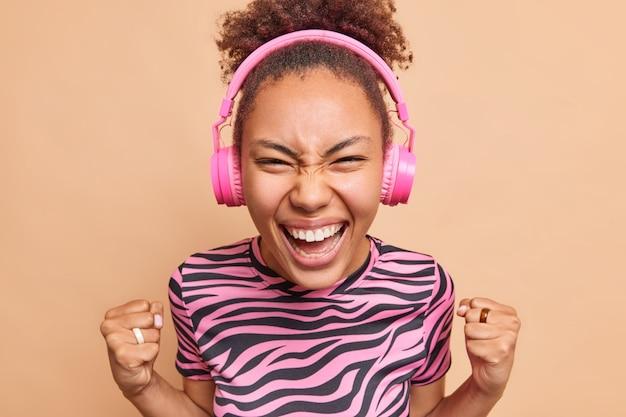 """Rozradowana nastolatka z kręconymi zaczesanymi włosami sprawia, że gest """"tak"""" trzyma pięści w górze, świętuje pomyślnie"""