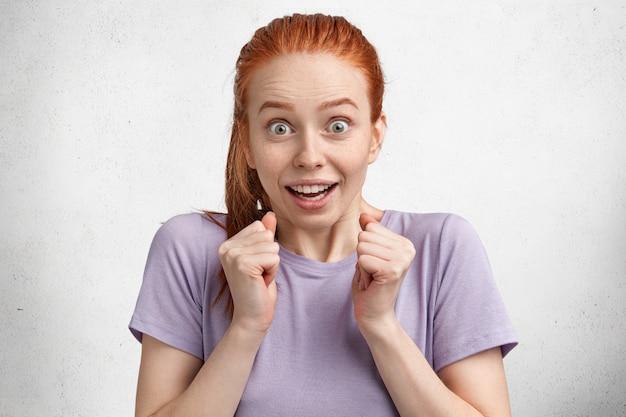 Rozradowana, podekscytowana rudowłosa modelka w fioletowym casualowym t-shircie, aktywnie gestykuluje, trzyma dłonie w pięści, demonstruje zaskoczoną reakcję na to, co słyszy