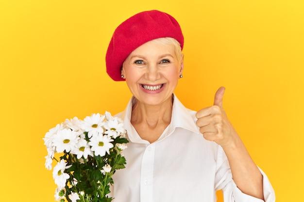Rozradowana, radosna kobieta w średnim wieku, ubrana w czerwoną czapeczkę z boku, pokazująca kciuki do góry, wyrażająca aprobatę, zachęcająca do kupowania kwiatów.