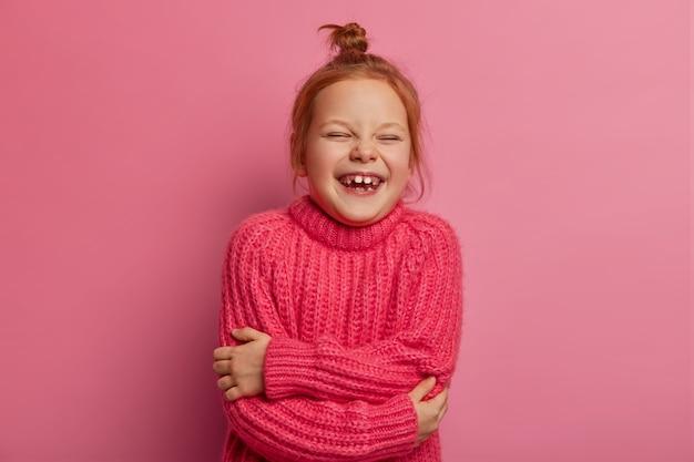 Rozradowana rudowłosa dziewczynka przytula się, ma pozytywny wyraz twarzy, nosi ciepły sweter z dzianiny, lubi sesję zdjęciową, wyraża szczere dobre emocje, odizolowana na różowej ścianie. dzieci, rozrywka