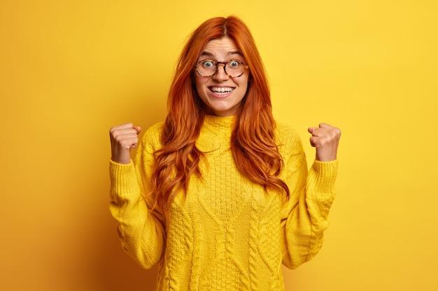Rozradowana, uradowana rudowłosa kobieta unosi zaciśnięte pięści i robi gest `` tak '' podekscytowana wspaniałymi wiadomościami, nosi okulary, a żółty sweter świętuje zdobycie stoisk z nagrodami w pomieszczeniach. koncepcja zwycięstwa sukcesu