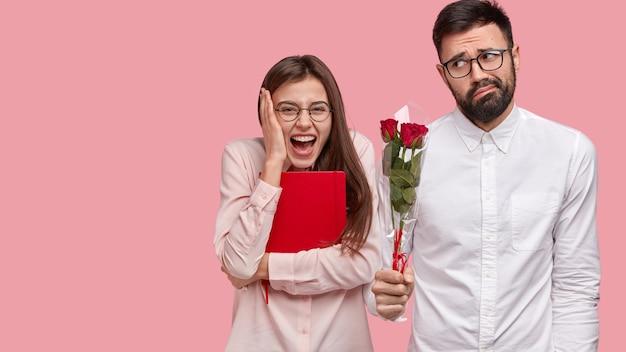 Rozradowana zadowolona kobieta ma pierwszą randkę, wyraża pozytywne emocje, obok stoi niezręczny facet z bukietem róż
