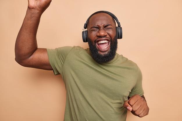 Rozradowany brodaty murzyn tańczy beztrosko, trzyma ręce w górze, porusza się w rytm muzyki, słucha muzyki przez słuchawki, ubrany w luźną koszulkę na białym tle nad brązową ścianą