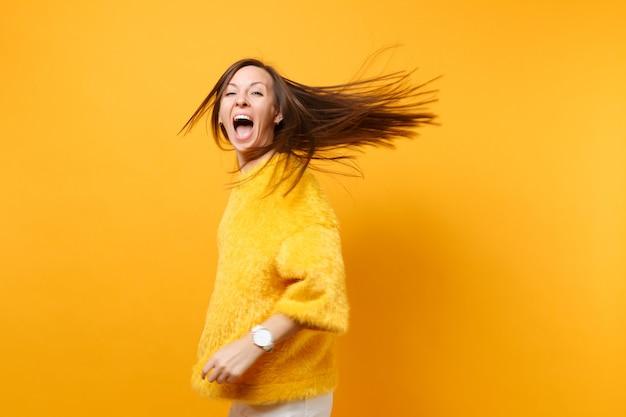 Rozradowany komiks młoda dziewczyna w futrzanym swetrze białych spodniach wirujących wygłupiać się w studio skoków z trzepoczącymi włosami na białym tle na żółtym tle. ludzie szczere emocje styl życia. powierzchnia reklamowa.