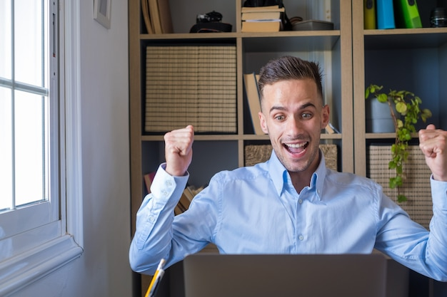 """Rozradowany mężczyzna z rasy kaukaskiej siedzi przy biurku, patrzy na ekran laptopa, czyta niesamowite wiadomości zaciskanie pięści sprawia, że gest """"tak"""" świętuje loterię hazardową wygrywanie, otrzymywanie nowej oferty pracy jest szczęśliwe"""