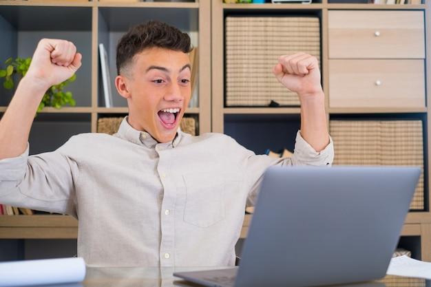 """Rozradowany nastolatek z rasy kaukaskiej siedzi przy biurku, patrzy na ekran laptopa, czyta niesamowite wiadomości zaciska pięści sprawia, że gest """"tak"""" świętuje wygraną na loterii online, otrzymanie nowej oferty pracy jest szczęśliwe"""