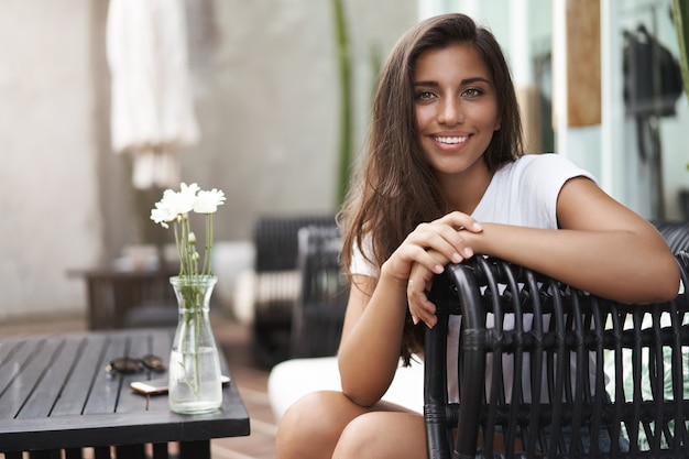Rozrywka, koncepcja dobrego samopoczucia. cudowna uśmiechnięta kobieta siedzi tak rattan