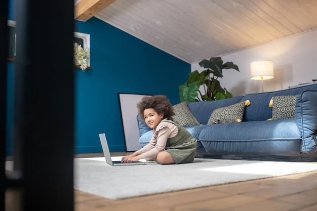 Rozrywka, laptop. mała uśmiechnięta ciemnoskóra dziewczyna siedzi z laptopem na podłodze w nowoczesnym, przytulnym pokoju w domu