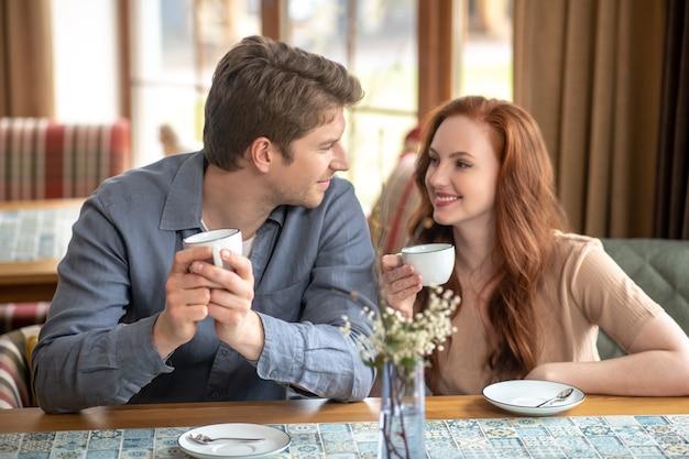 Rozrywka. młoda kobieta z długimi rudymi włosami i atrakcyjnym mężczyzną pije kawę na czacie w restauracji po południu