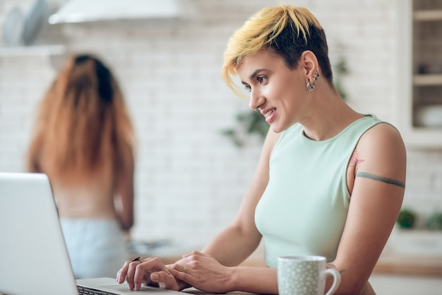 Rozrywka. uśmiechnięta młoda dorosła ładna kobieta na laptopie i ciemnoskóra dziewczyna z powrotem w kuchni