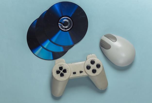Rozrywka w stylu retro. staromodna mysz komputerowa, gamepad i płyty cd na niebiesko