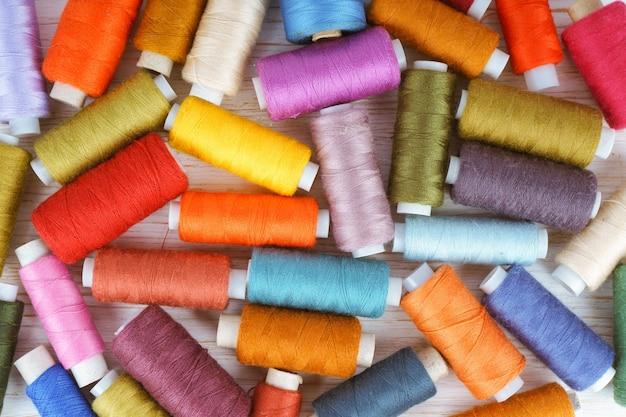 Rozrzucanie różnych kolorów nici do szycia na białym drewnianym stole. widok płaski, widok z góry.