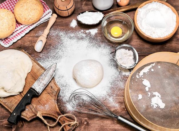Rozrzucona mąka pszenna na stole, obok surowego ciasta drożdżowego