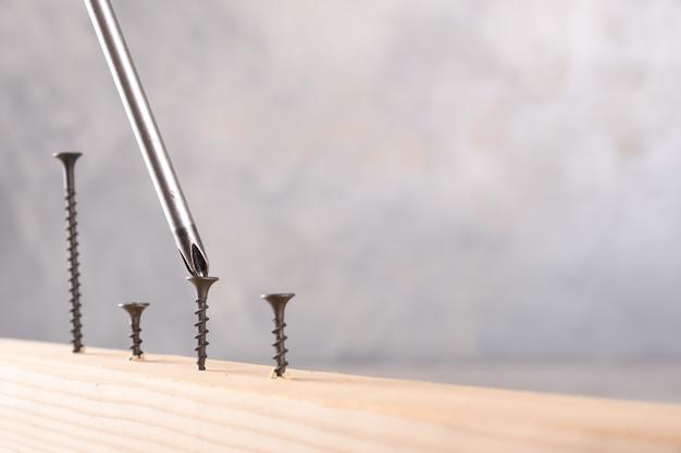 Rozrzucona śruba wkręcona śrubokrętem w drewnianą deskę