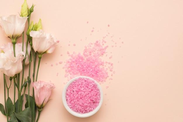 Rozrzucona wokół misy różowa sól do kąpieli i delikatne kwiaty na tle brzoskwiniowego koloru