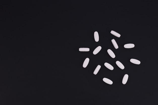 Rozrzucone białe pigułki na czarnym tle z miejscem na tekst. pojęcie medyczne.