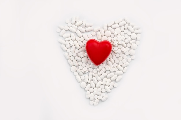 Rozrzucone białe tabletki z czerwonym sercem, odizolowane