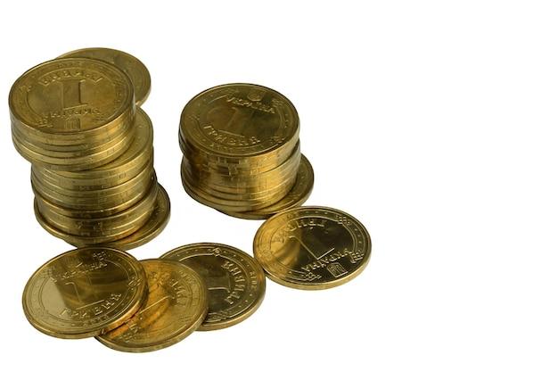 Rozrzucone błyszczące żółte żelazne monety i stosy na białym tle