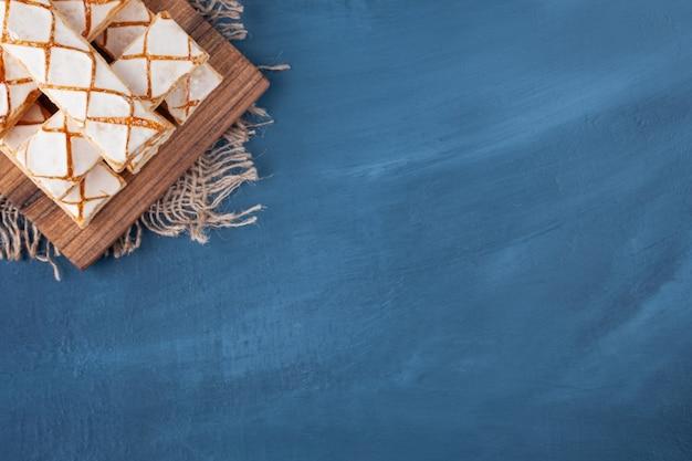 Rozrzucone ciasteczka waflowe ułożone na drewnianej desce.