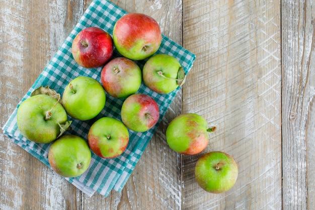Rozrzucone jabłka na drewnianej i piknikowej szmatce.