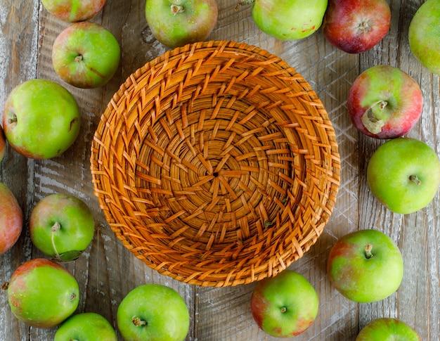 Rozrzucone jabłka z pustym koszem na drewnie