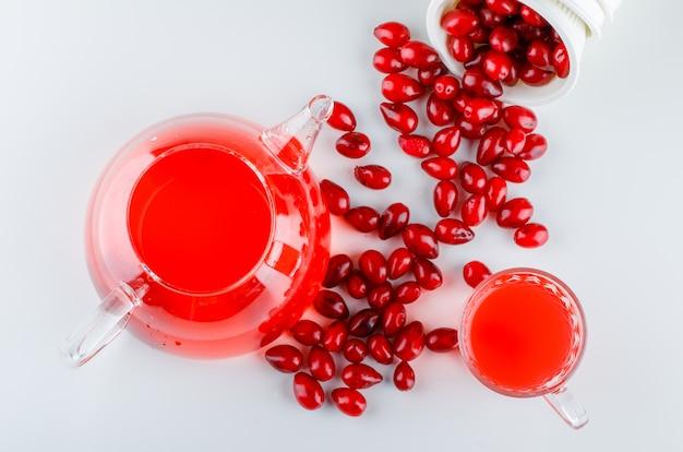 Rozrzucone jagody dereń z miski z napojem na białym tle