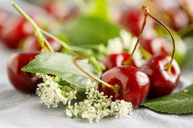 Rozrzucone jagody i wiśnia liście na drewnianym białym tle