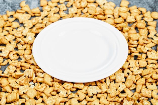 Rozrzucone krakersy alfabetu wokół pustego talerza.