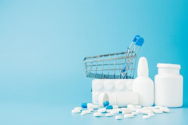 Rozrzucone odmiany pigułki, leki, spay, butelki, termometr, strzykawki i pusty wózek wózek na zakupy na niebieskim tle. koncepcja zakupy apteka