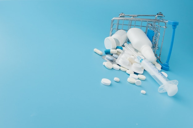 Rozrzucone pigułki, narkotyki, spay, butelki, termometr, strzykawka i pusty wózek na zakupy. koncepcja zakupy apteka
