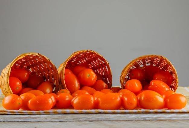 Rozrzucone pomidory z koszy z widokiem z boku tkaniny piknikowej na szarej i drewnianej przestrzeni