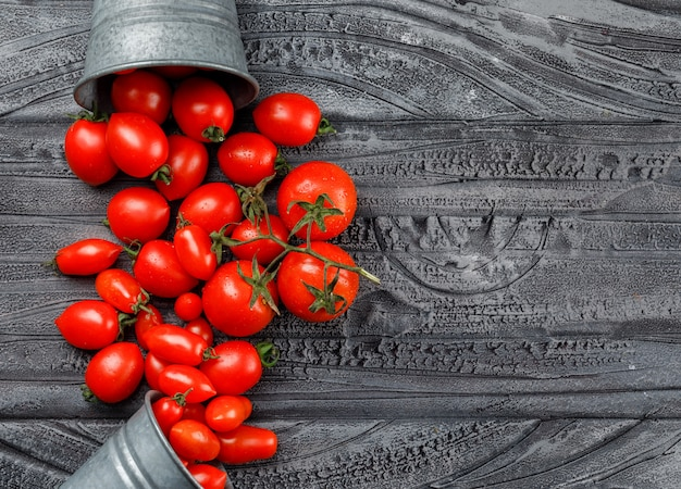Rozrzucone pomidory z wiader mini na szarej drewnianej ścianie. widok z góry.
