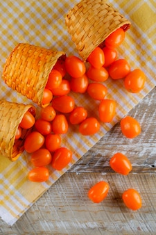 Rozrzucone pomidory z wiklinowych koszy na piknikowym obrusie i drewnianym stole. widok z góry.