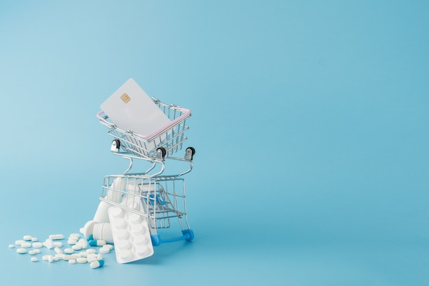 Rozrzucone rozmaitość pigułki, leki, spay, butelki, termometr, strzykawka i pusty wózek wózek na zakupy na niebieskim tle. koncepcja zakupy apteka