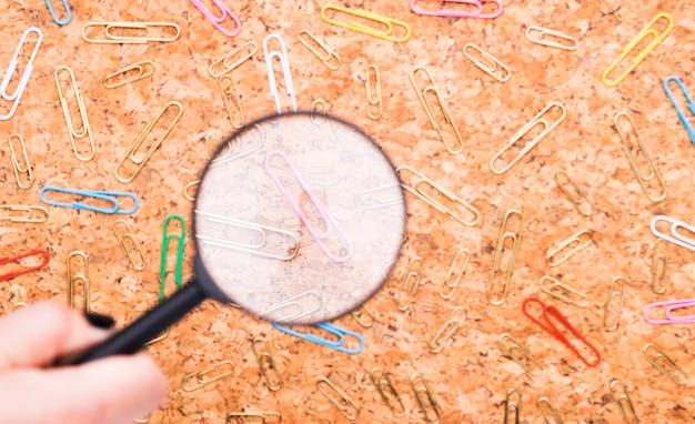 Rozrzucone spinacze do papieru zbadane przez szkło powiększające na tle pokładzie korka