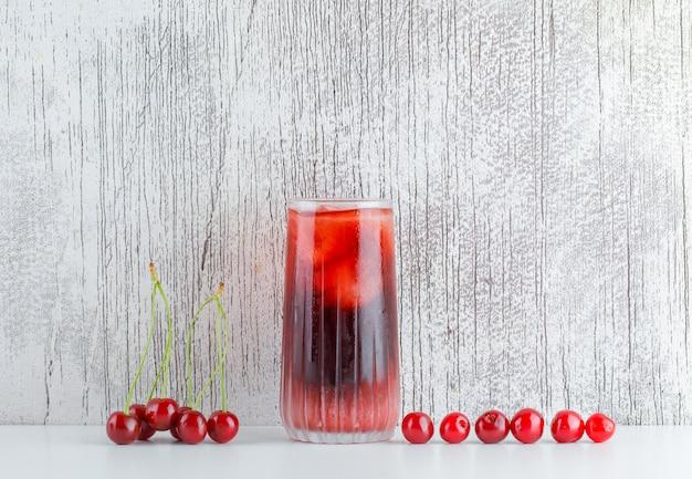 Rozrzucone wiśnie z lodowatym napojem na białym i nieczysty stole, widok z boku.
