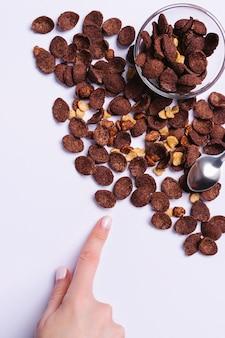 Rozrzucone zboża kakaowe na ostatecznym szarym tle z pustą przestrzenią i ręką pokazującą palec wskazujący.