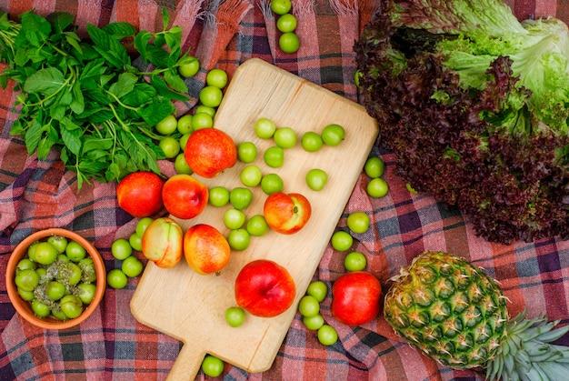 Rozrzucone zieleniny i brzoskwinie z zielonymi liśćmi, ananasem i sałatą w desce do krojenia i glinianej misce na materiale piknikowym, leżą płasko.