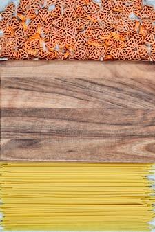 Rozrzucony makaron w kształcie serca i spaghetti wokół drewnianej deski.