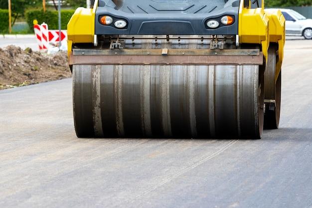Rozściełacz asfaltu na drodze podczas zagęszczania asfaltu z bliska. remont dróg. układanie nowej drogi