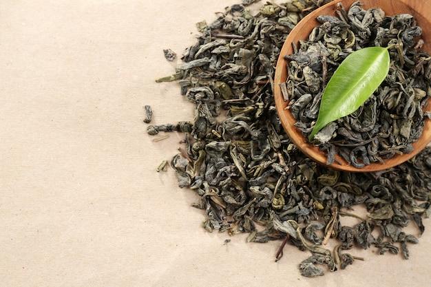 Rozsypana herbata z zielonymi liśćmi w drewnianej łyżce na płótnie