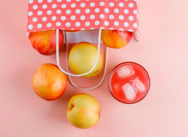 Rozsypane nektarynki z sokiem z papierowej torby na różowym stole, leżące na płasko.