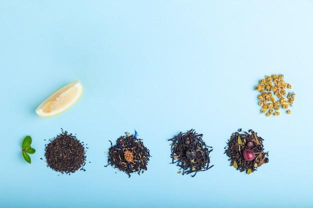 Rozsypiska różna czarna i ziołowa herbata na błękitnym tle