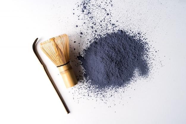 Rozsypisko matcha błękitnej herbaty proszek i bambusowy chasen odizolowywający na białym tle