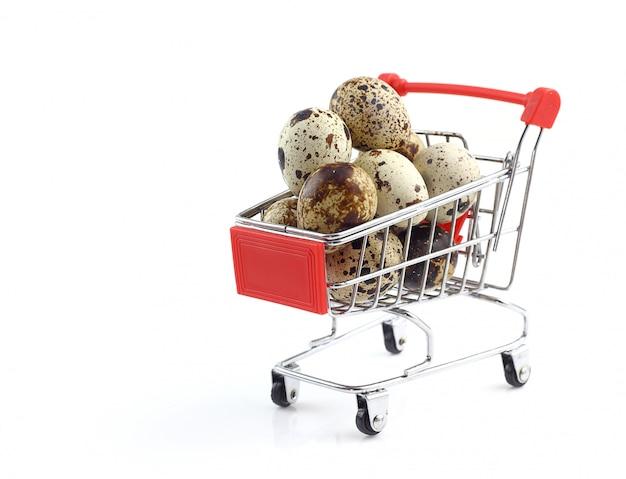 Rozsypisko przepiórek jajka w wózek na zakupy odizolowywającym na bielu
